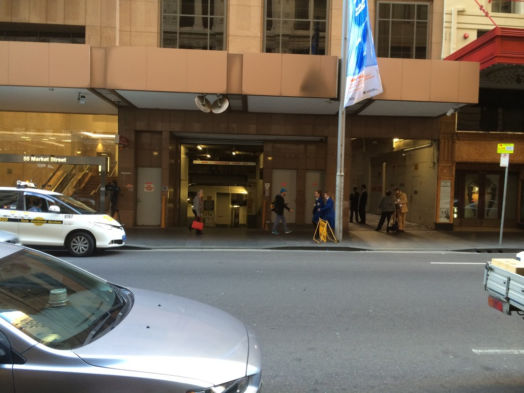 The Commision venue on left, the cafe on the right, and the laneway in the middle with 2 people smoking